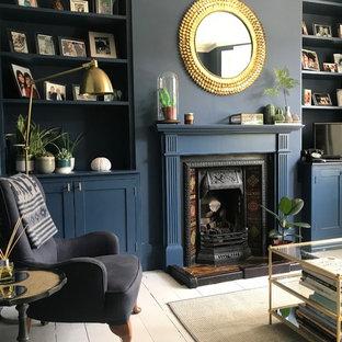 ロンドンの小さいヴィクトリアン調のおしゃれな独立型リビング (青い壁、塗装フローリング、標準型暖炉、木材の暖炉まわり、白い床) の写真
