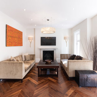 Design ideas for a large contemporary enclosed living room in Hertfordshire with grey walls, dark hardwood flooring, a standard fireplace, a stone fireplace surround, a wall mounted tv and brown floors.