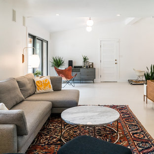 Example of a mid-sized danish enclosed concrete floor and beige floor living room design in Austin with white walls and a wall-mounted tv
