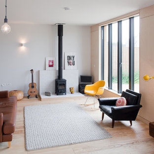 Example of a danish open concept light wood floor living room design in London with white walls, a wood stove and a tv stand