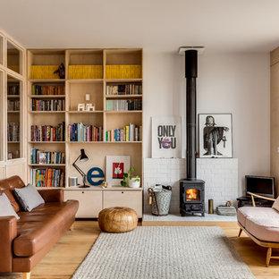 Imagen de salón abierto, escandinavo, de tamaño medio, con paredes blancas, suelo de madera clara y estufa de leña