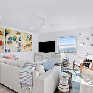 タンパの小さいビーチスタイルのおしゃれなLDK (白い壁、セラミックタイルの床、壁掛け型テレビ、ベージュの床) の写真