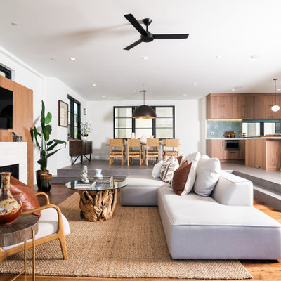 Inspiration for a contemporary open concept medium tone wood floor and brown floor living room remodel in Los Angeles with white walls, a standard fireplace, a brick fireplace and a wall-mounted tv