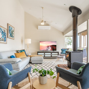 Transitional enclosed living room in Melbourne with white walls, a wood stove, no tv, beige floor and vaulted.