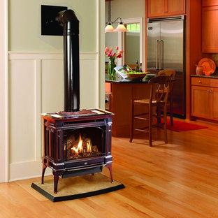 Idee per un soggiorno american style aperto con pareti verdi, parquet chiaro, stufa a legna e pavimento marrone