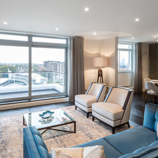 Contemporary open plan living room in London with beige walls, dark hardwood flooring and a wall mounted tv.