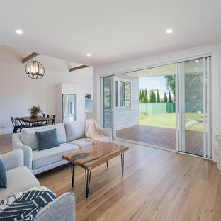 Design ideas for a transitional open concept living room in Newcastle - Maitland with white walls, medium hardwood floors, a wall-mounted tv and beige floor.