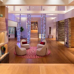 Foto de salón abierto, contemporáneo, grande, con paredes blancas, suelo de madera en tonos medios y suelo marrón