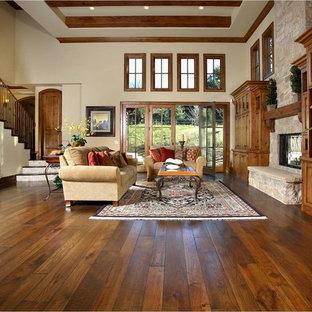 Immagine di un soggiorno chic con cornice del camino in pietra e pavimento marrone
