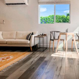 Пример оригинального дизайна: маленькая парадная, открытая гостиная комната в скандинавском стиле с коричневым полом, бежевыми стенами, полом из ламината и отдельно стоящим ТВ без камина