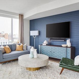 Ejemplo de salón para visitas abierto, retro, grande, con paredes azules, suelo de madera clara, suelo beige y televisor colgado en la pared