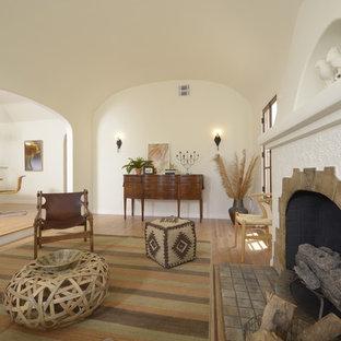 Immagine di un soggiorno mediterraneo di medie dimensioni e aperto con sala formale, pareti bianche, parquet chiaro, camino classico e cornice del camino piastrellata