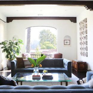 ロサンゼルスの広い地中海スタイルのおしゃれな独立型リビング (フォーマル、白い壁、濃色無垢フローリング、標準型暖炉、タイルの暖炉まわり、テレビなし、茶色い床) の写真