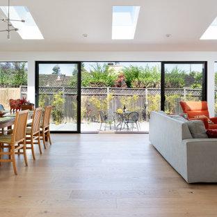 Foto de salón abierto, contemporáneo, grande, sin chimenea, con paredes blancas, suelo de madera clara, televisor colgado en la pared y suelo amarillo