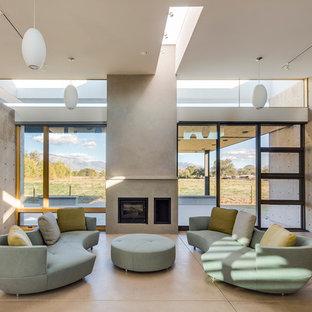 Modernes Wohnzimmer mit grauer Wandfarbe, Betonboden, Kaminumrandung aus Metall, Kamin und Wand-TV in Albuquerque