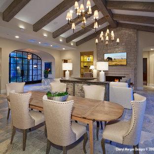 Foto di un ampio soggiorno country aperto con angolo bar, pareti beige, pavimento in travertino, camino classico, cornice del camino in pietra e TV a parete