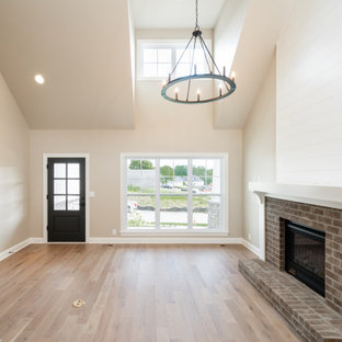 Example of an arts and crafts open concept light wood floor, brown floor, vaulted ceiling and shiplap wall living room design in Louisville with white walls, a standard fireplace and a brick fireplace