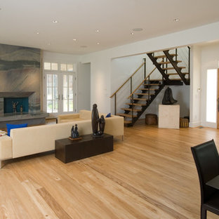 Large midcentury formal open concept living room in Other with white walls, light hardwood floors, a standard fireplace, a stone fireplace surround, no tv and brown floor.