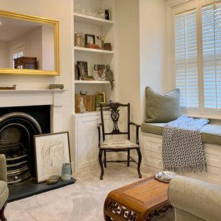 Esempio di un grande soggiorno boho chic con sala formale, pareti beige, moquette, camino classico, cornice del camino in cemento, TV a parete e pavimento verde