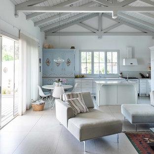他の地域の小さいビーチスタイルのおしゃれなリビング (白い壁、磁器タイルの床、薪ストーブ、漆喰の暖炉まわり、壁掛け型テレビ、白い床) の写真
