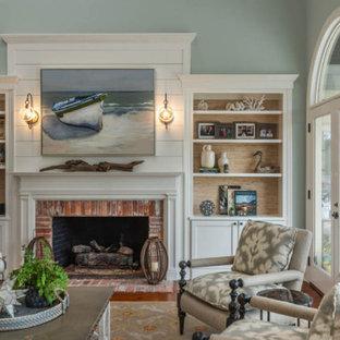 アトランタのビーチスタイルのおしゃれなリビング (緑の壁、無垢フローリング、標準型暖炉、レンガの暖炉まわり、据え置き型テレビ、茶色い床) の写真