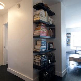 Immagine di un piccolo soggiorno minimalista aperto con pareti bianche, parquet scuro, TV a parete e pavimento nero