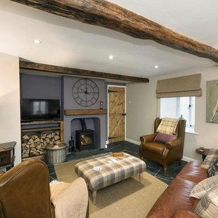 Esempio di un soggiorno tradizionale di medie dimensioni e chiuso con pareti viola, pavimento in ardesia, stufa a legna, cornice del camino in legno, TV autoportante e pavimento nero