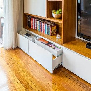Modelo de salón abierto, contemporáneo, grande, sin chimenea, con paredes blancas, suelo de madera en tonos medios y televisor colgado en la pared