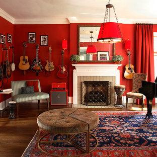 アトランタのエクレクティックスタイルのおしゃれなリビング (ミュージックルーム、赤い壁、濃色無垢フローリング、標準型暖炉、石材の暖炉まわり) の写真