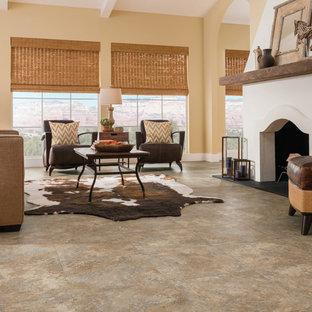 Diseño de salón para visitas abierto, clásico renovado, grande, sin televisor, con suelo de piedra caliza, chimenea tradicional, paredes amarillas, marco de chimenea de yeso y suelo beige