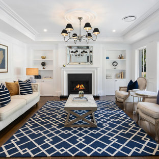 Large beach style formal open concept living room in Sydney with white walls, a standard fireplace, a concrete fireplace surround, dark hardwood floors, brown floor, recessed and panelled walls.
