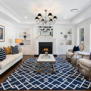 Cette image montre un grand salon marin ouvert avec une salle de réception, un mur blanc, une cheminée standard, un manteau de cheminée en béton, un sol en bois foncé, un sol marron, un plafond décaissé et du lambris.
