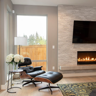 Example of a huge 1950s open concept light wood floor and beige floor living room design in Seattle with gray walls, a standard fireplace, a stone fireplace and a wall-mounted tv