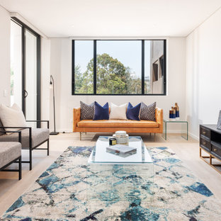 This is an example of a small transitional formal open concept living room in Sydney with white walls, light hardwood floors, a freestanding tv, no fireplace and beige floor.