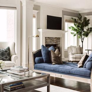 Diseño de salón para visitas abierto, clásico renovado, grande, con paredes grises, suelo de madera en tonos medios, chimenea tradicional, marco de chimenea de piedra y televisor independiente