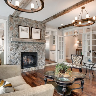 Photo of a large classic formal enclosed living room in Minneapolis with grey walls, a two-sided fireplace and a stone fireplace surround.