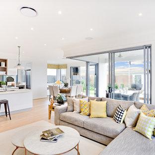 Diseño de salón con barra de bar tipo loft, minimalista, de tamaño medio, sin chimenea y televisor, con paredes blancas, suelo de madera en tonos medios y suelo amarillo