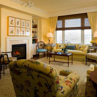 Imagen de salón para visitas abierto, clásico, de tamaño medio, sin televisor, con paredes amarillas, suelo de madera oscura, chimenea tradicional, marco de chimenea de piedra y suelo marrón