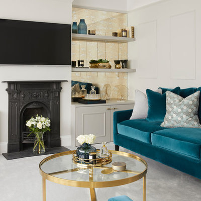 Inspiration for a mid-sized transitional enclosed carpeted and gray floor living room remodel in Hertfordshire with gray walls, a wall-mounted tv, a wood stove and a metal fireplace