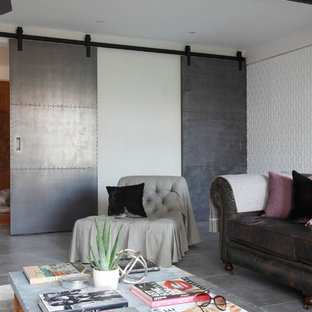 This is an example of a medium sized industrial living room in London with concrete flooring.