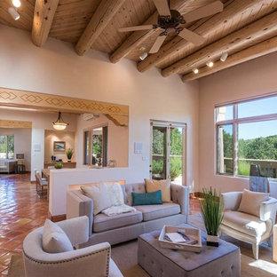 他の地域の広いサンタフェスタイルのおしゃれな独立型リビング (白い壁、テラコッタタイルの床、コーナー設置型暖炉、漆喰の暖炉まわり、テレビなし、オレンジの床) の写真
