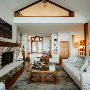 Ejemplo de salón con rincón musical abierto, moderno, grande, con paredes marrones, suelo de madera en tonos medios, chimenea tradicional, marco de chimenea de piedra y suelo marrón