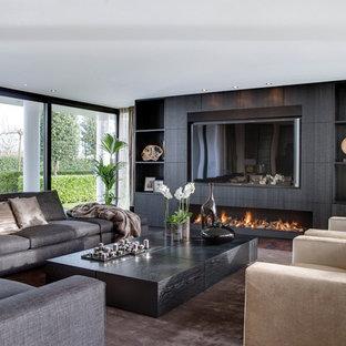 Exempel på ett modernt vardagsrum, med en bred öppen spis och en inbyggd mediavägg