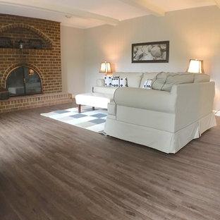 Inredning av ett klassiskt mellanstort separat vardagsrum, med ett finrum, beige väggar, vinylgolv, en standard öppen spis och en spiselkrans i tegelsten