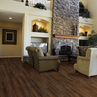 Inspiration for a large classic formal enclosed living room in Other with beige walls, vinyl flooring, a standard fireplace, a stone fireplace surround, a built-in media unit and brown floors.