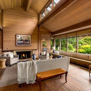 Idées déco pour un très grand salon asiatique avec un sol en bois brun, une cheminée standard et un manteau de cheminée en pierre.