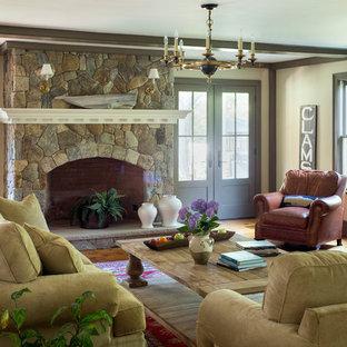Esempio di un grande soggiorno country aperto con pareti beige, parquet chiaro, cornice del camino in pietra, nessuna TV, sala formale e camino classico