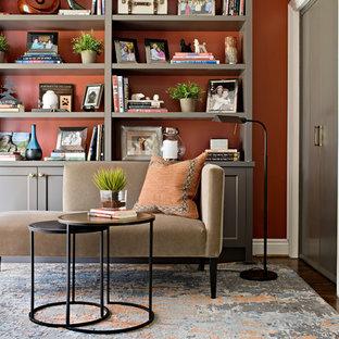 Ejemplo de biblioteca en casa cerrada, clásica renovada, pequeña, sin chimenea y televisor, con parades naranjas, suelo de madera oscura y suelo marrón