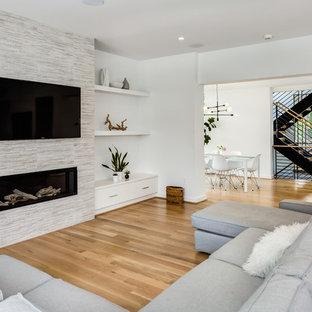 Modelo de salón abierto, minimalista, grande, con paredes blancas, suelo de madera clara, chimenea lineal, marco de chimenea de piedra, televisor colgado en la pared y suelo beige