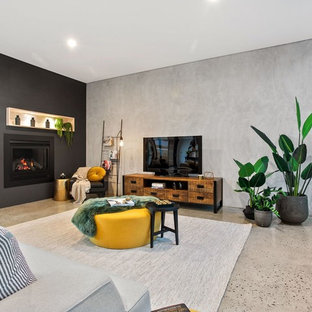 Contemporary living room in Perth with grey walls, concrete floors, a standard fireplace, a freestanding tv and grey floor.